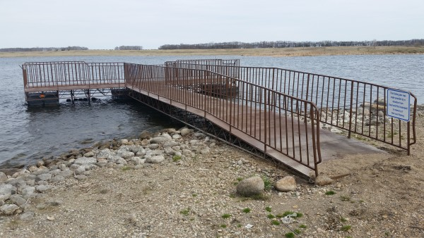 View of floating metal fishing pier from shoreline looking out over lake.