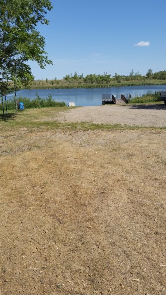 Looking from designated parking area down to boat landing and fishing pier showing gravel base and incline to parking.