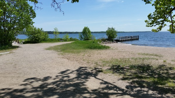 Picture from the parking area looking towards the fishing pier right of rocks behind trees