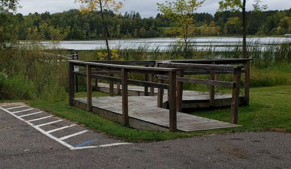 View looking past an accessible parking area and onto the ramp leading to the fishing pier.