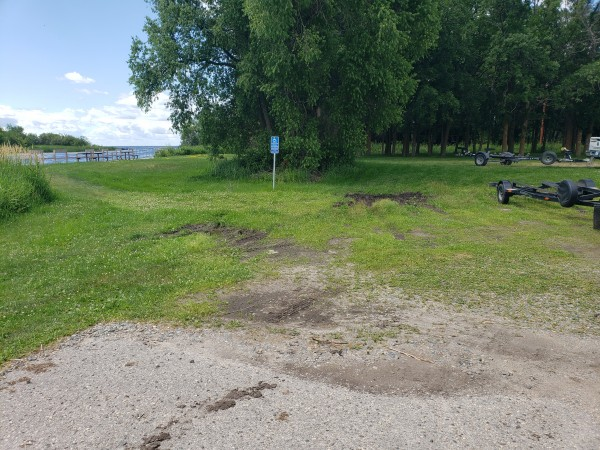 From fishing ramp vehicle approach looking at accessible parking signage with fishing platform in background to left of parking space.  Notice the deep ruts.