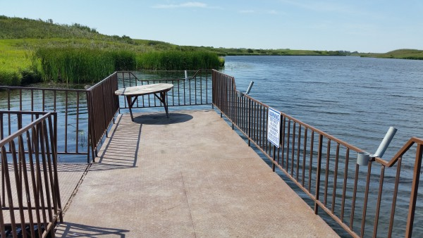 Looking across gravel roadway/parking area to T shaped pier.